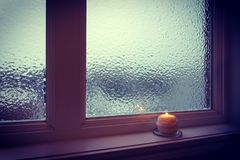 Candle burning near a frosted window in twilight. Winter evening Stock Images