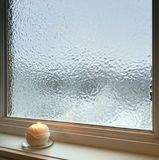 Candle burning near frosted window. Weather after freezing rain Royalty Free Stock Photography