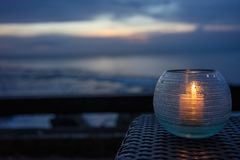 Candle burning in the night with ocean background, romantic mood stock images