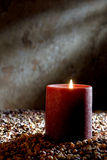 Candle Burning with Soft Glow Flame in Old House. Pillar candle burning with a soft glowing flame on a bed of pea gravel in an old house or church for meditation stock image