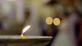 The candle burns in the church. The back background is blurred stock footage