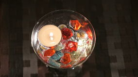 Candle burns in a glass with scattered gemstones stock video