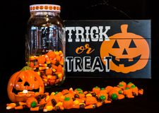Halloween Display. A candle burns in the jack-o-lantern while some candy corn is poured out on the table and some remains in the glass jar royalty free stock photos