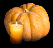 The candle burns and pumpkin on a black background Stock Photo