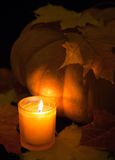 Candle burns and pumpkin with maple leaf Royalty Free Stock Photos