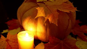 The candle burns before pumpkin and maple leaves on dark background stock video footage