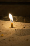 Candle. Burns in the sand stock photography