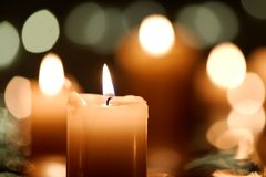 Candle with candlelight bokeh. Burning candle with defocused candlelight background Stock Image