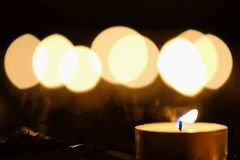 Candle and candlelight. Burning candle against defocused background of candlelight Stock Photo