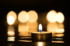 Candle and candlelight. Single candle burning in darkness with reflection of candlelight in the background Royalty Free Stock Image