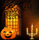 Candle in a candlestick and a pumpkin on a backgro Stock Photography