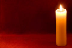 Candle on carmine Stock Photos