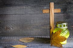 Candle and cemetery cross on wooden background in autumn Stock Image