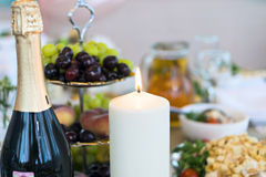 Candle and champagne buttle on table Royalty Free Stock Photos