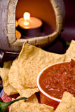 Candle, chips and salsa. Closeup view of mexican oven with lit candle and tortilla chips and salsa stock image