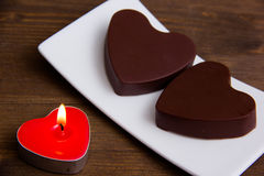Candle and chocolates in a heart shape on wood close Stock Image