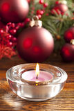 Candle and christmas baubles and tree Royalty Free Stock Photography
