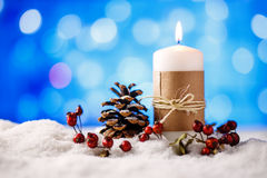 Candle and christmas decoration in snow with blue light background. Royalty Free Stock Image