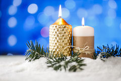 Candle and christmas decoration in snow with blue light background. Stock Image