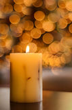 Candle with Christmas tree in background. Royalty Free Stock Photo