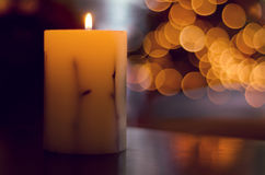 Candle with Christmas tree in background. Stock Image