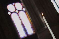 Candle in a church. Single candle in a church with the stained-glass window in the background Royalty Free Stock Image
