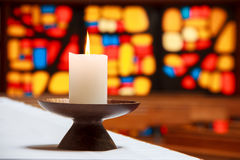 Candle in a church with a mosaic. Burning candle in a church with the stained-glass window at the background. Location: New Zealand, North Island, Wellington Stock Images