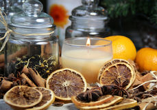 Candle, cinnamon sticks and dry orange Stock Images