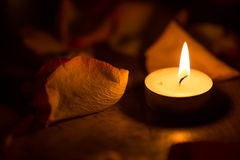 Candle close up and rose petals. Stock Photos