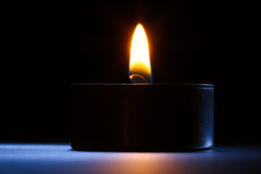 Candle closeup on the desk. Black-blue background. Royalty Free Stock Image