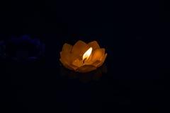 Candle colorido amarelo de Beautyful da flor na água, fundo preto Fotos de Stock Royalty Free