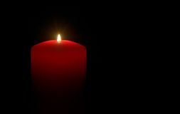 Candle in the dark. A red candle over a black background Royalty Free Stock Images