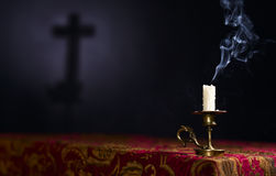 Candle on a dark background with the silhouette of the cross Stock Image