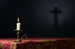 Candle on a dark background with the silhouette of the cross Royalty Free Stock Images
