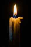 Candle in a dark. Classic white candle on fire Stock Images