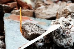 Candle in debris of red bricks from demolished house in focus Stock Photos