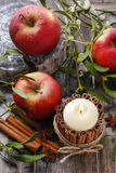 Candle decorated with cinnamon sticks, apples and mistletoe Royalty Free Stock Photography