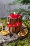 Candle decorated with cinnamon sticks and dried fruits around Royalty Free Stock Photos