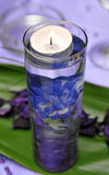 Candle in a decorated glass with water Stock Photos