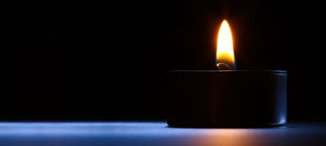 Candle on the desk. Black-blue background. Royalty Free Stock Photography