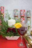 Candle display in a ceramic pot + fern for Christmas. Candle display in a ceramic pot plus a fern branches with a dark red bow for Christmas, also Glass of wine Royalty Free Stock Image