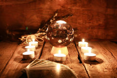 Candle divination tarot cards. Crystal ball for predicting the fate and supernatural action on the table from the old mahogany with candles and cards Royalty Free Stock Images