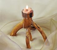 Original wooden candle stick. The candle on the drapery of Stock Photos