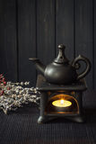 Candle driven aroma lamp diffuse essential oils. For Aromatherapy or Esoterics. Dark background, Black on black colors Stock Image
