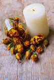 Candle And Dry Rose Buds On Wood Background Royalty Free Stock Photo