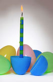 Candle in an Easter Egg. A single lighted Birthday candle in an Easter Egg, surrounded by more Easter Eggs Stock Images