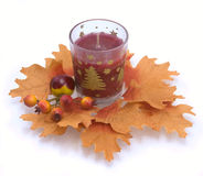 Candle in an environment of autumn leaves Stock Photo