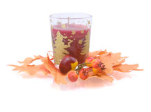 Candle in an environment of autumn leaves. New Year's candle in an environment of autumn leaves on white background Royalty Free Stock Photography