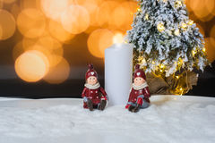 Candle and figures with Christmas tree against light background.  Stock Images