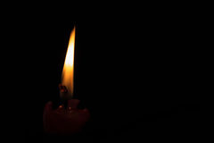 Candle fire in the night. A lonely candle burning in  the darkness Royalty Free Stock Photos